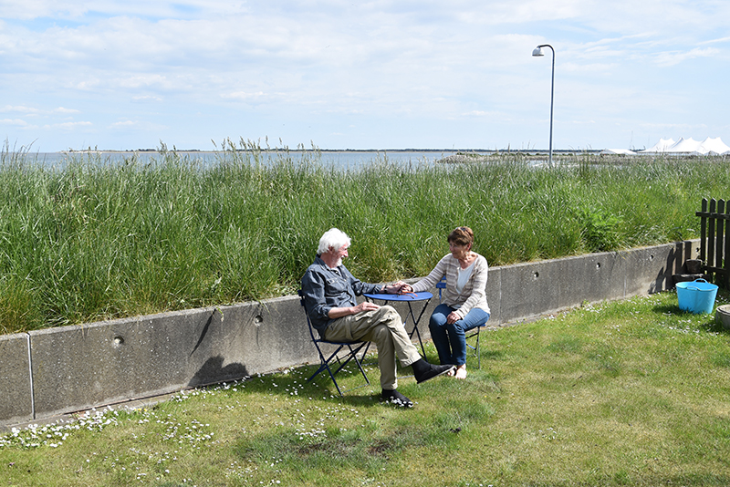 Inge og Christian Poulsen i haven, der er beskyttet af diget i Nordby.