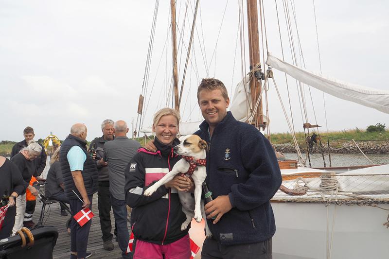 Louise Petersen og Rasmus Sonnichsen blev modtaget af venner og familie med flag og øl på havnen i Nordby. De havde hunden Pippi med hjem, som de havde fundet på gaden på Saint Martin.