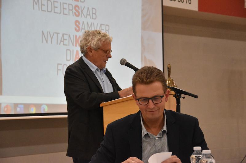 Formand Hans Mathiasen på talerstolen. Foran ham ses brugsuddeler Bent Kruse Madsen.