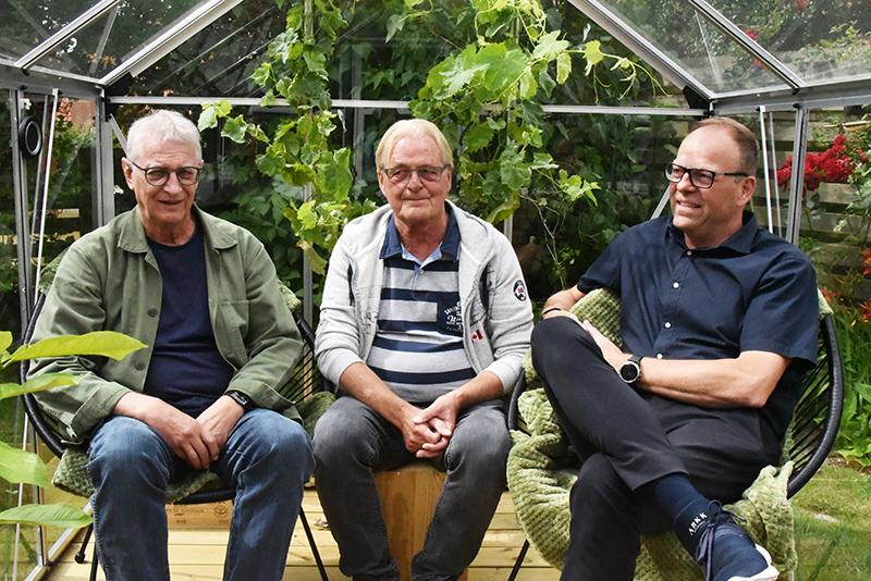 John Birk i midten har fået sig et dejligt drivhus i sin have.