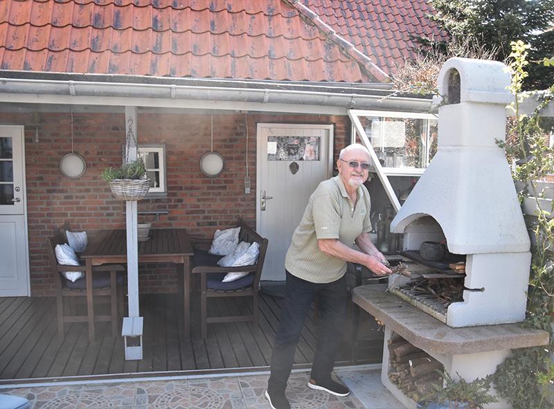 Hans Peder ved den udendørs grill i baghaven.