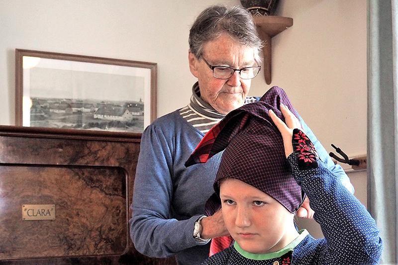 """Gertrud Nærø, der bor i Sønderho, sætter klude på Asta-Marie Friborg Rudloff, mens hun synger: """"Det er en ære fanødragt at bære"""". Hun var været kludebinderske i flere år."""