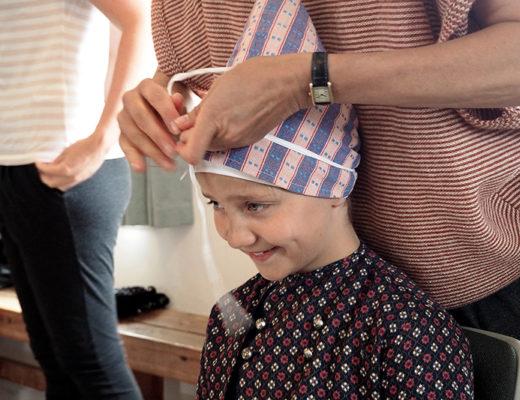 Formanden for Fonden Gamle Sønderho, Susanne Winsløw, hjælper Ronja Thomsen Østerlund med tørklædet. Ronja er 11 år og bor i Hadsten. Hun kommer i Sønderho, fordi hendes mormor har sommerhus i byen.