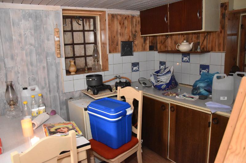 Stue-køkken-arrangementet. Der er lidt mørkt på grund af lukkede skodder. Af uransagelige grunde har der lige været indbrud.